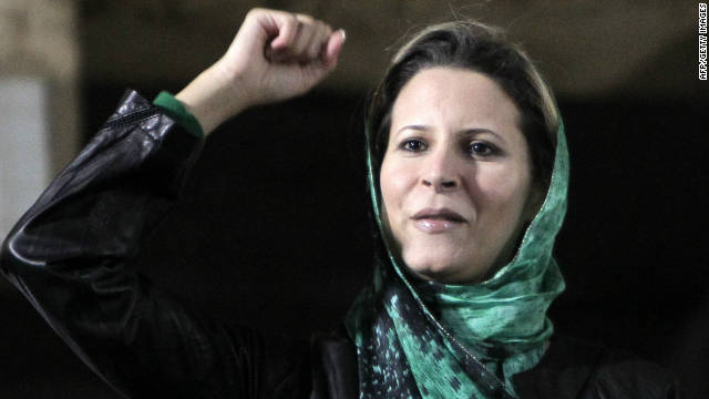 Aisha, daughter of Moammar Gadhafi, salutes the crowds gathered in her father's residence in Tripoli on April 15, 2011.