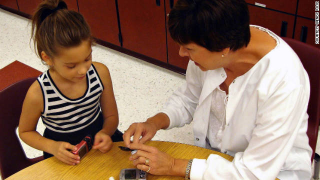 Adalyne Rose tests her blood glucose levels with the help of her school nurse, Carla Moore.