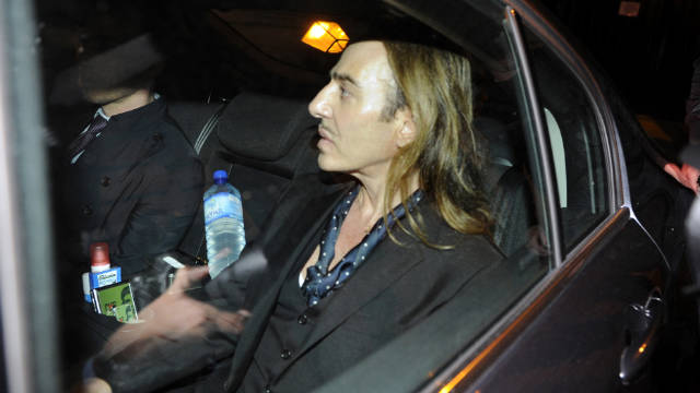 "This June 22, 2011 file photo shows fashion designer John Galliano as he leaves in a car after he stood trial for anti-Semitic insults in a Paris' court. John Galliano, the flamboyant fashion designer who fell from grace after an anti-Semitic outburst in Paris, has said making supermodel Kate Moss' wedding gown this summer was his ""creative rehab."""