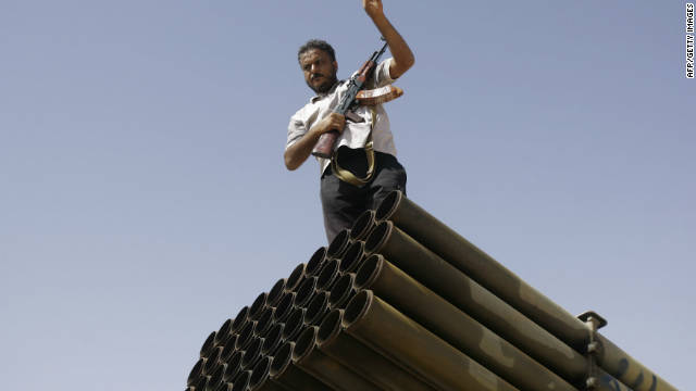 A Libyan NTC fighter poses for a photo on top of a Grad missile launcher on the outskirts of Bani Walid.