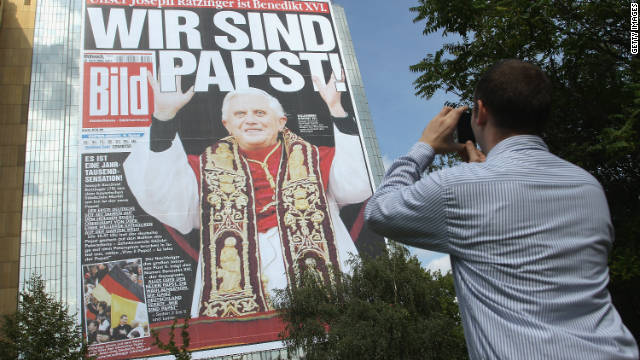 A man takes a picture of a giant reproduction picturing the front page of tabloid Bild Zeitung the day after Joseph Ratzinger was appointed Pope Benedict XVI in 2005 hanging on the facade of the Axel Springer Verlag headquarters on September 20, 2011 in Berlin