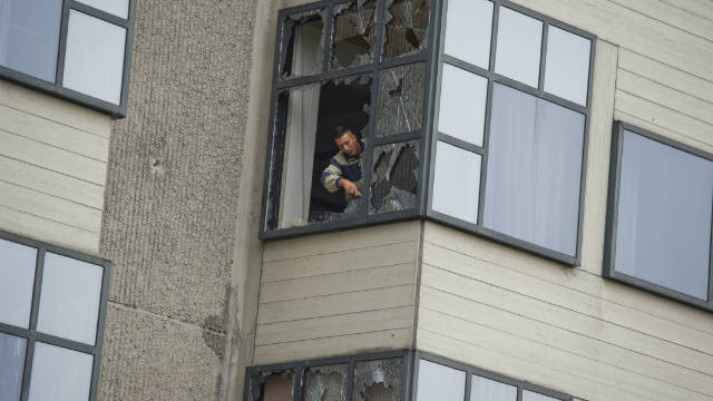 A worker removes glass from a window of an Amsterdam courthouse following the explosion in the early hours of the morning.