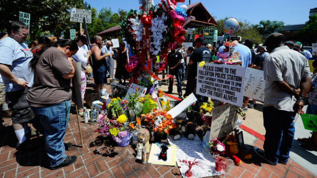 Demonstrators hold a moment of silence at a makeshift memorial for Kelly Thomas, a homeless man who died after an altercation with several police officers in Fullerton, California.