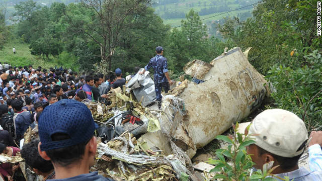 Onlookers and rescuers are seen near the wreckage of the aircraft in Lalitpur, on the outskirts of Kathmandu, on September 25.