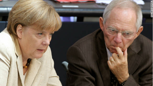 German Chancellor Angela Merkel (L) sits next to German Finance Minister Wolfgang Schauble