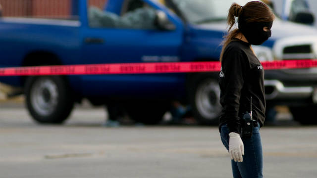 A member of Mexico's Ministerial Police investigates the scene of a murder in Ciudad Juarez on December 6, 2010. FILE