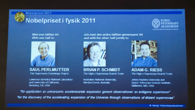 A giant screen in Stockholm shows the joint winners of the Nobel Prize in physics for 2011.