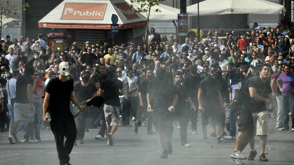 Demonstrators clash with police in the face of tear gas. The protests are part of a 24-hour general strike in the public sector that shut down Athens International Airport, government ministries and schools. Hospitals operated on skeleton staffs, and some commuter rail services were closed.