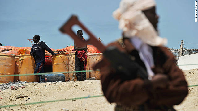 A pirate folds his arms over his weapon near two boys on a beach in the Somali town of Hobyo on August 20, 2010.
