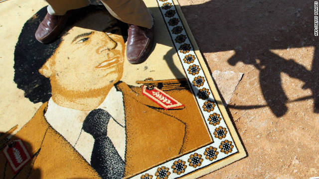 A National Transitional Council fighter stands on a small rug with a portrait of Moammar Gadhafi at the frontline in Bani Walid.