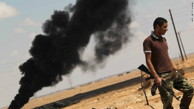 A National Transitional Council fighter walks past a plume of black smoke at the frontline in Bani Walid on October 4.