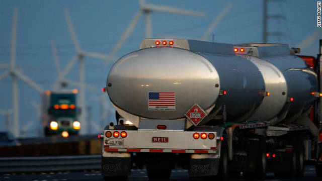 Emissions-producing diesel trucks pass non-polluting wind turbines along Interstate 10 in Banning, California.