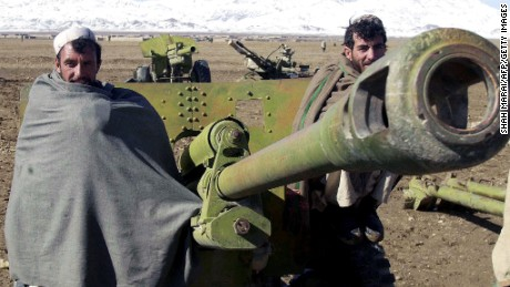 GARDEZ, AFGHANISTAN:  Afghan militiamen Bakhtyar, 37, (R) and Ali Shah , 39, (L) pose in front of a 80 mm rocket launcher during a disarmament cermony in Gardez, the capital of Paktia province, 17 November 2003. About 600 Afghan militiamen handed in their guns in the latest phase of an ambitious disarmament program. AFP PHOTO/SHAH Marai  (Photo credit should read SHAH MARAI/AFP/Getty Images)