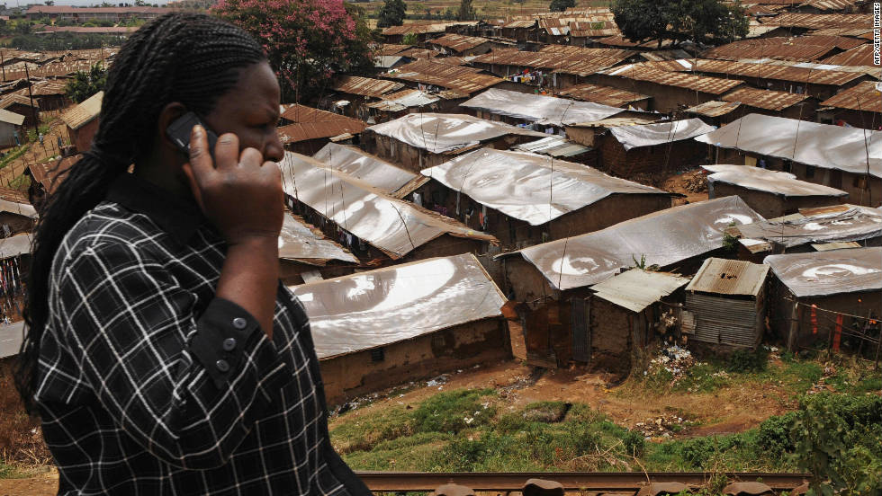 A woman speaks on a mobile phone in front of Kibera, one of the world's largest slums, on February 16, 2009, near Nairobi. Mobile phone growth in Africa has grown more than 400% from 2005 to 2010.