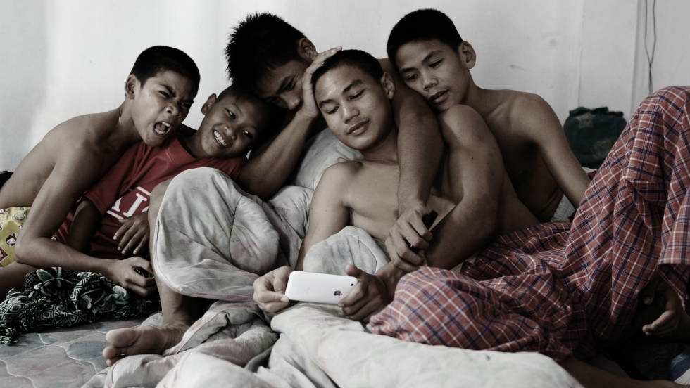 "Thai orphans gather around watching videos on an iPhone at the Phuwana Muay Thai Kickboxing Camp on October 4, 2008, an hour outside of Bangkok. ""Increased mobile connectivity in schools, as you can imagine, has had a profound effect,"" said economist Jeffrey Sachs."