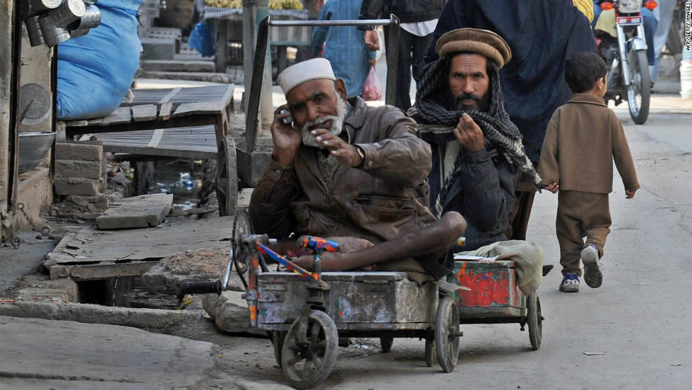 A disabled  beggar looks on as another beggar talks on a mobile phone in a market in Rawalpindi, Pakistan, on November 19, 2008. A 2006 University of Michigan study found that every 10% increase in cell phone penetration grows the local economy by 0.6%.