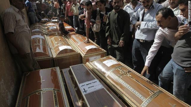 Egyptians gather at the coffins of some of the 24 Coptic Christians killed during over night clashes on October 10.
