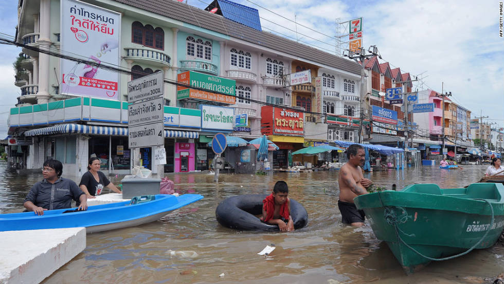 Thai residents stand in floodwaters along a street in the city of Ayutthaya on October 6, 2011.
