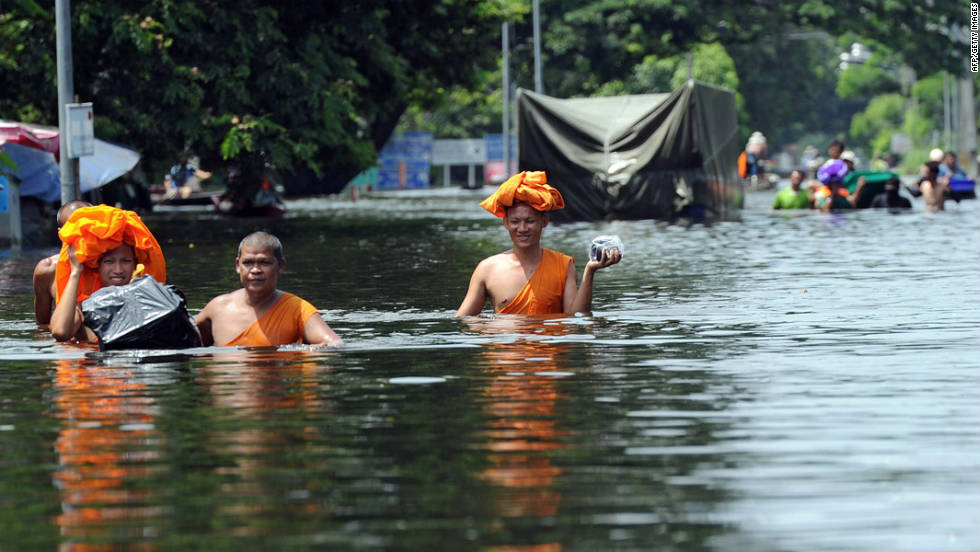 Buddhist monks walk through high water as floods inundate Ayutthaya province on October 10, 2011.