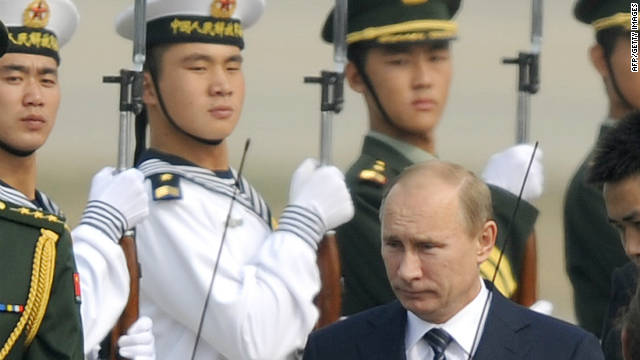 Russia's Prime Minister Vladimir Putin walks past an honor guard after arriving at Beijing International Airport on October 11.