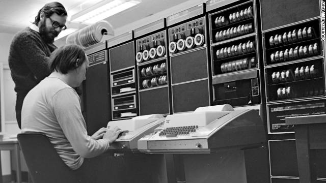Dennis Ritchie stands over Ken Thompson as he works on the PDP-11 in 1972.