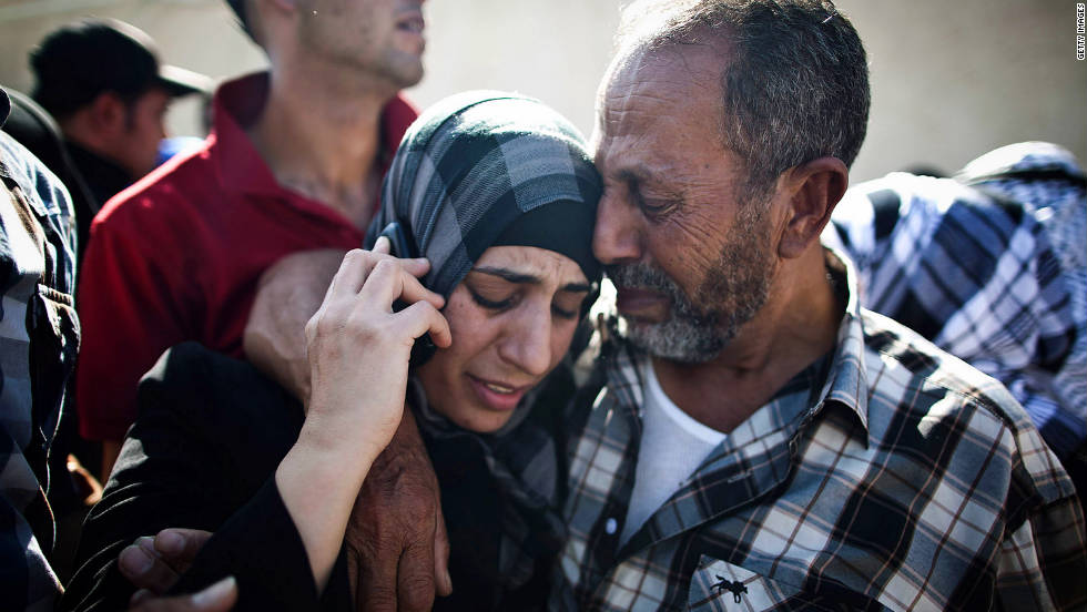 A Palestinian prisoner hugs relatives as she speaks on a mobile phone in Ramallah, West Bank, following her release on Tuesday.