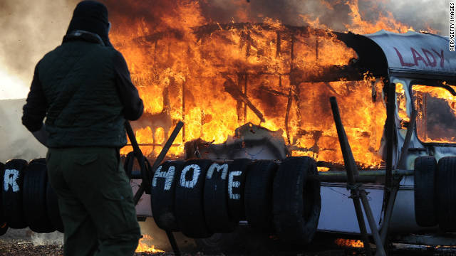 A caravan burns as riot police begin evicting travellers and their supporters from Dale Farm near Basildon, east of London.