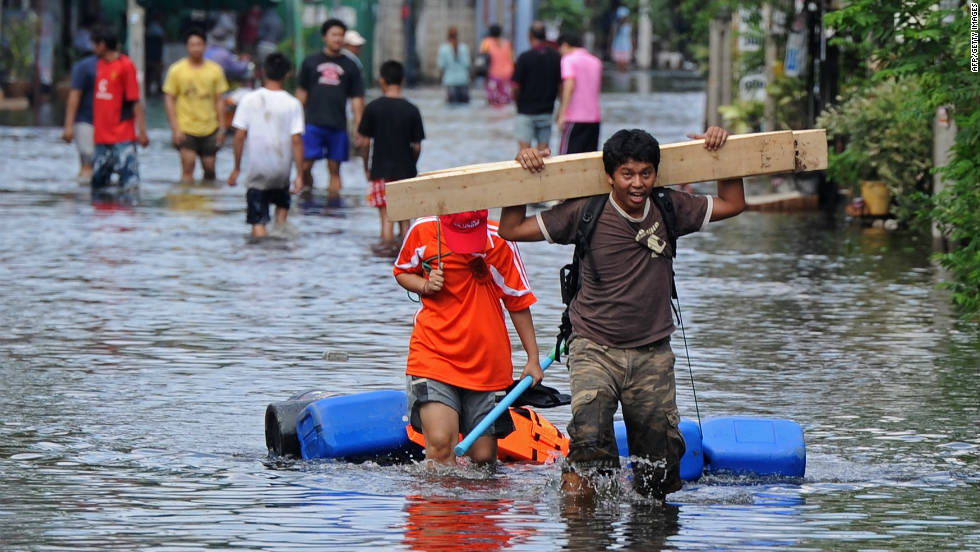 Residents carry their belongings through floodwaters in Bangkok on October 21.