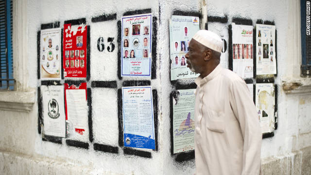 A Tunisian man walks past a wall covered with posters of political candidates on Bourguiba Avenue in Tunis.