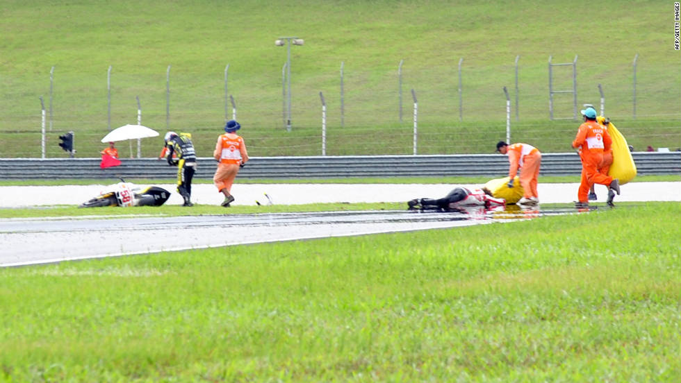 Marshalls rush to assist Simoncelli after he crashed on his Honda (no58) at Sepang.