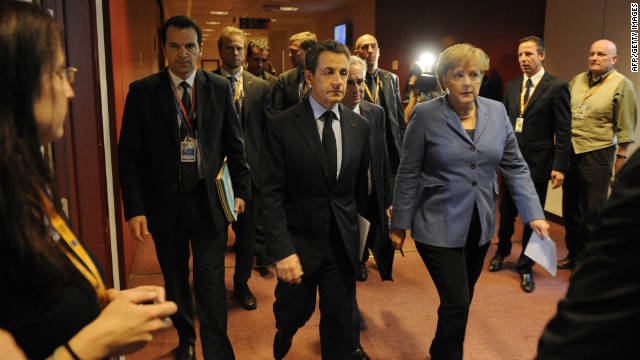 German Chancellor Angela Merkel (C) and French President Nicolas Sarkozy (L) walk in a corridor on their way to a joint press conference as part of the European Council at the Justus Lipsius building, EU headquarters in Brussels on October 23, 2011. Sarkozy said that 'broad agreement' was reached to ramp up the firepower of the eurozone rescue fund, at a summit of European Union leaders.