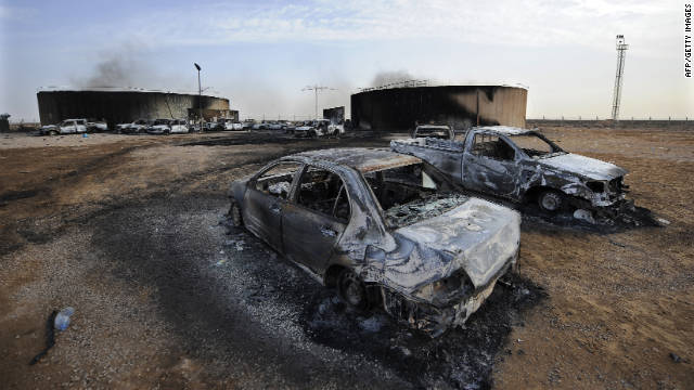 Charred cars sit at the site of a blast in Sirte, Libya, on Tuesday. More than 100 people were killed.