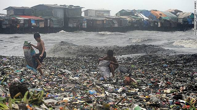 Children looking for usable materials among the garbage after a typhoon in Manila Bay, Philippines.