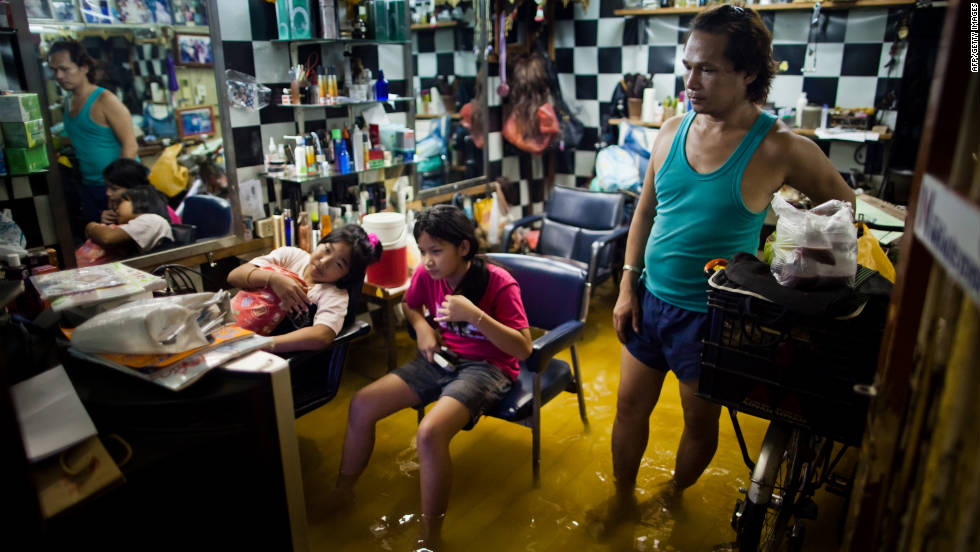 Bangkok residents watch television in a flooded beauty salon on Wednesday.