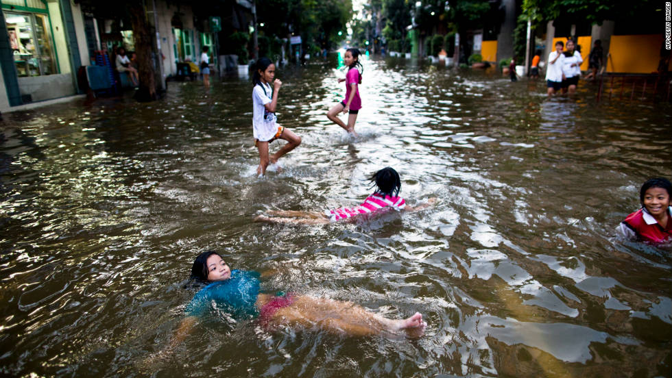 Children play in flooded streets in Bangkok. It might take more than a month for the waters to recede in some areas, officials say.