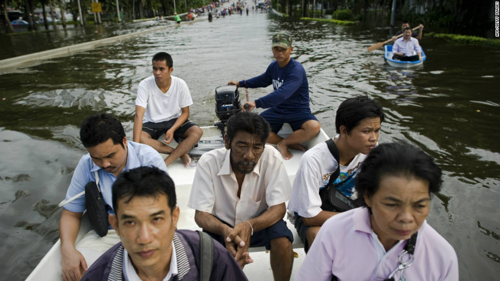 People travel through floodwaters on a boat as they evacuate their neighbourhood next to the Chao Praya river in Bangkok..