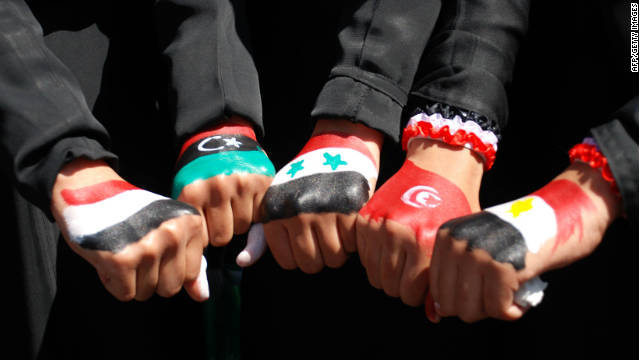 Yemenis women show off their fists painted in the colors of five Arab national flags