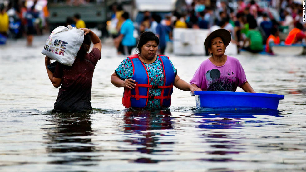 Thai residents wade through waist-high waters in Bangkok on Friday, October 28, after heavy floods swept through the area. Hundreds of people have died from flood-related incidents since July.