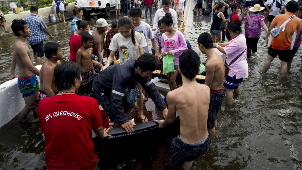 Residents evacuating their neighborhoods get off a rescue boat near the Chao Praya River.