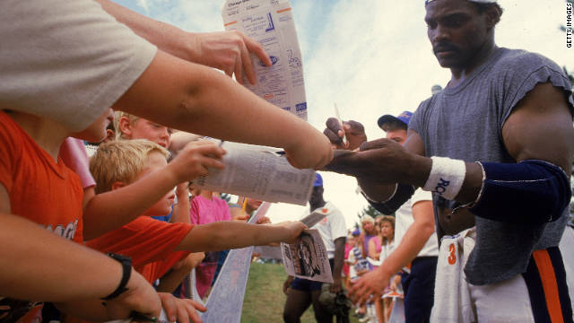 Walter Payton, #34 of the Chicago Bears, signs autographs during training camp in 1987