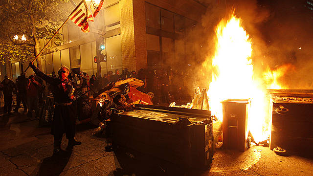The Occupy Oakland protesters set a fire on trash to make a barricade as the police officers form a line to disperse the protesters on November 3, 2011 in Oakland, California. AFP Photo/ Kimihiro Hoshino (Photo credit should read KIMIHIRO HOSHINO/AFP/Getty Images)