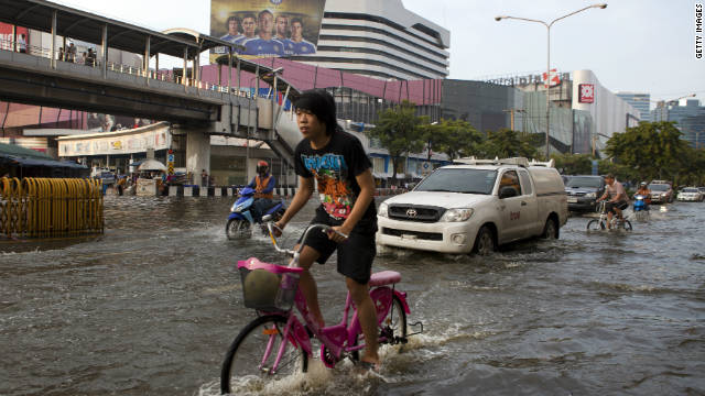 A Thai man rides his bicycle as flood waters take over the streets in a major shopping and business district  in Bangkok.