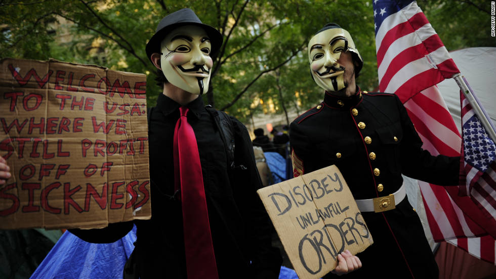 Masked Occupy Wall Street supporters hold signs at Zuccotti Park in New York on October 30.