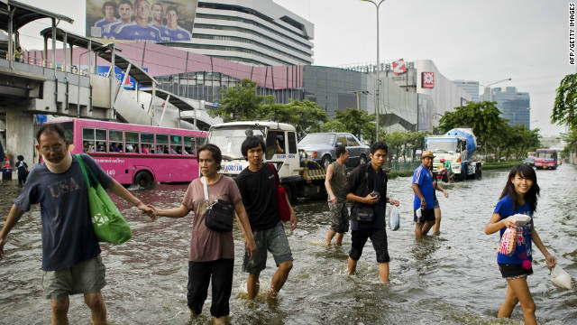 People walk through the flooded streets in Lat Phrao shopping and business district in Bangkok, Thailand, on November 5, 2011.