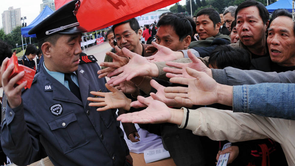 A group of Chinese men gather to collect the free condoms distributed to mark World AIDS Day in Fujian province on December 1, 2010.