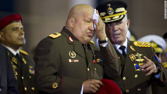 Venezuelan President Hugo Chavez (C) dries his face next to Defense Minister Carlos Mata Figueroa (R) during a military ceremony in the National Army Academy in Caracas on November 6, 2011. AFP PHOTO / Leo RAMIREZ (Photo credit should read LEO RAMIREZ/AFP/Getty Images)