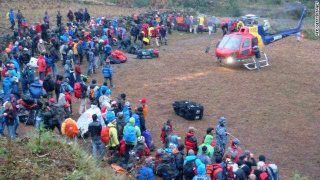 Tourists wait to be rescued by private helicopter from the village of Surke near Lukla, on November 5 2011.