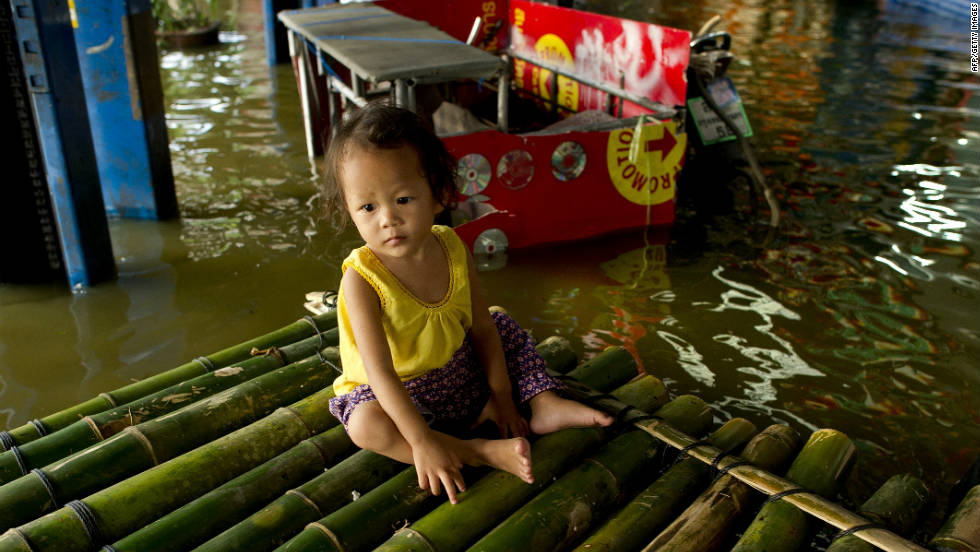 A baby sits on a bamboo raft in flood waters in Lat Phrao shopping and business district in Bangkok on November 7.