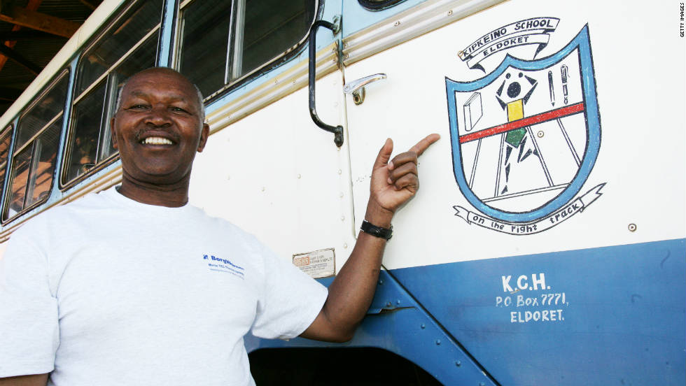 Keino poses beside a bus with the mural of his primary school in Eldoret, Kenya.