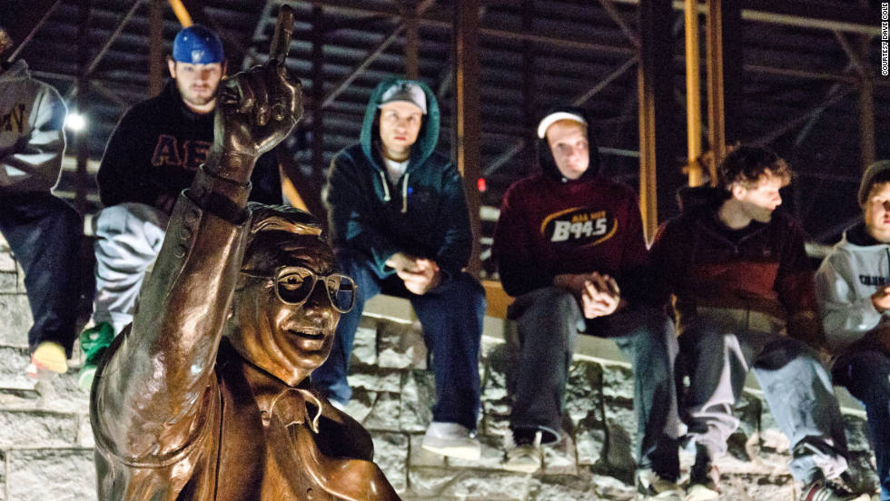 Students visit the Joe Paterno statue adjacent to Beaver Stadium to quietly honor the legendary coach following the announcement that he was fired.